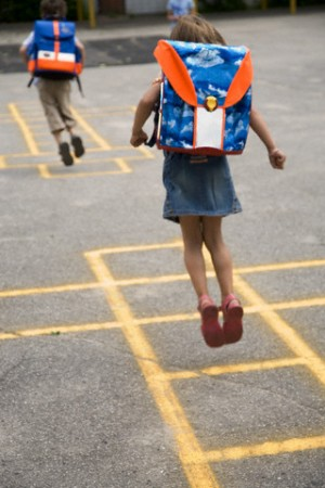 Girl with Schoolbag Playing Hopscotch